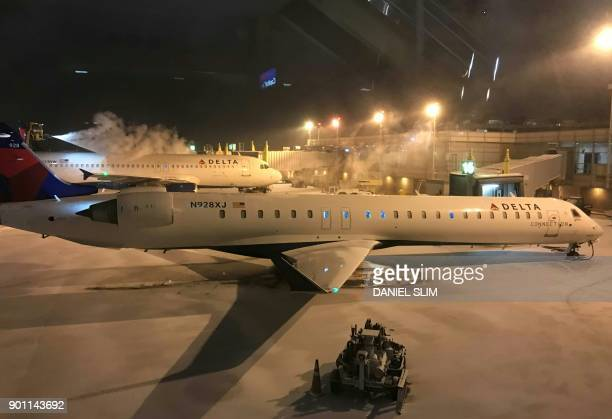 Two planes sit on the tarmac at Ronald Reagan airport near Washington DC one of them a Delta Airbus being deiced before departure January 4 2018 The...