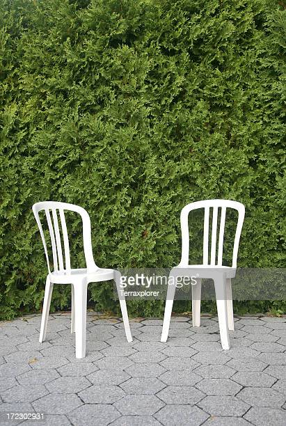 Two Plastic Chairs In Front Of Hedges
