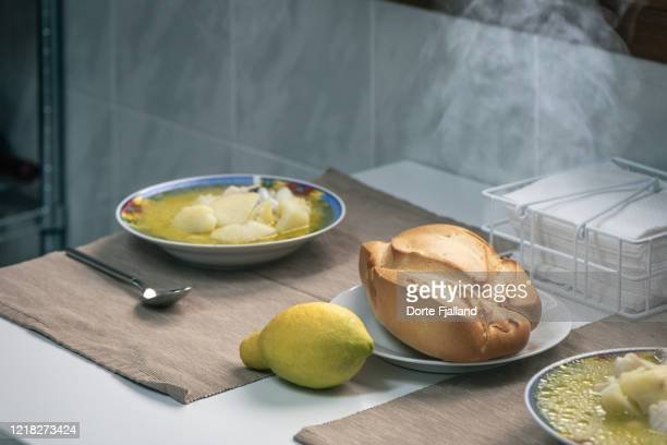 two plates of fish and potato soup, bread and a lemon on a table - dorte fjalland stock pictures, royalty-free photos & images