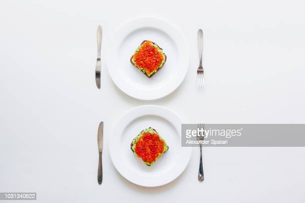 Two plates with avocado toasts and red caviar, directly above view