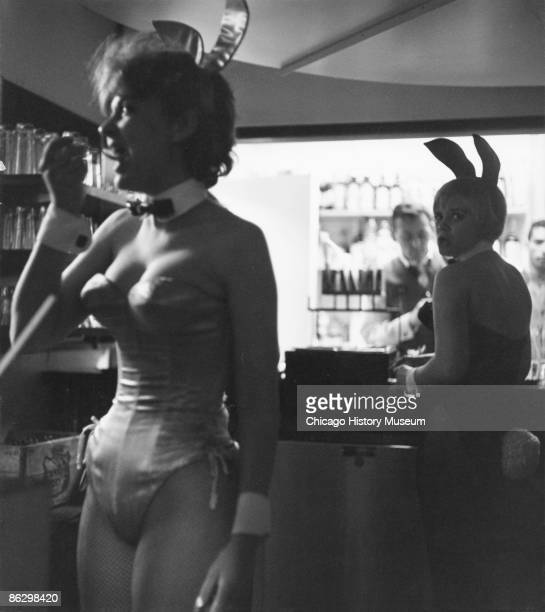 Two Playboy bunnies at work at the Playboy Club one is seen having a snack while the other waits for an order at the bar Chicago ca1960s Two...