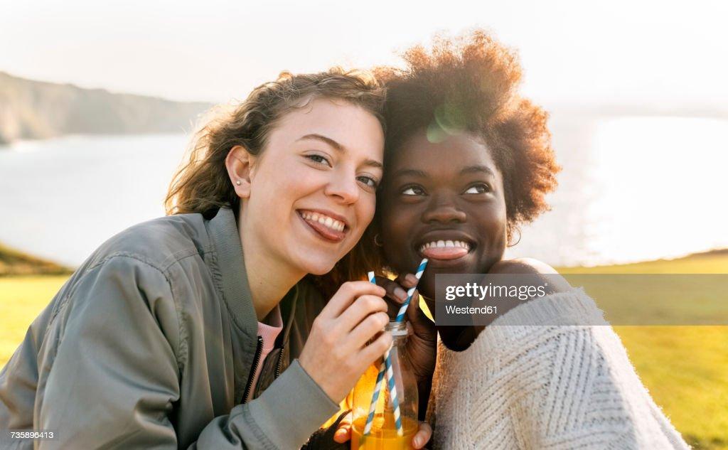 Two playful best friends drinking orange juice outdoors : Stock Photo