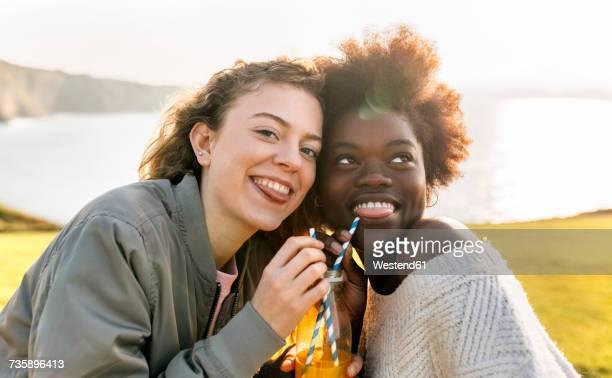 Two playful best friends drinking orange juice outdoors