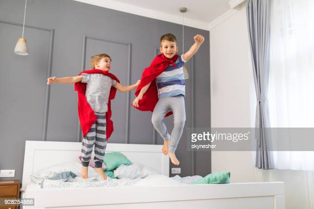 Two playful boys having fun while jumping on a bed and pretending to be superheroes.