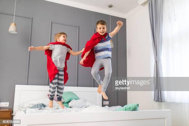Deux garçons ludique s'amuser tout en sautant sur un lit et faire semblant d'être des super héros.