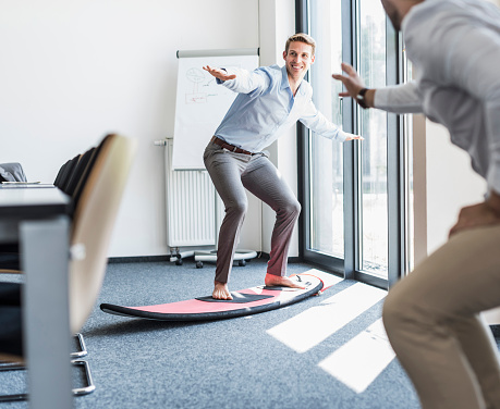 Two playful colleagues with surfboard in office - gettyimageskorea