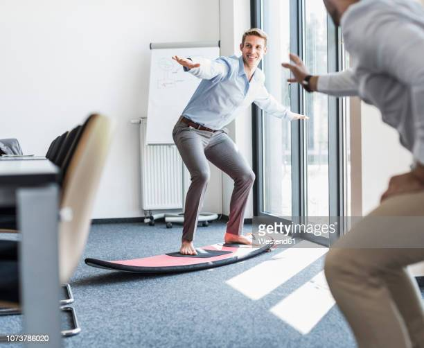 Two playful colleagues with surfboard in office