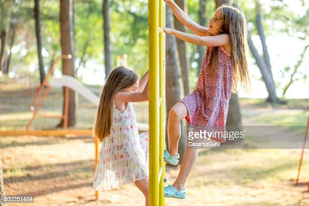 Two Playful Girls Climbing Metal Bar At The Playground