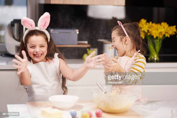 two playful sisters having fun baking easter cookies in kitchen together - pasqua foto e immagini stock