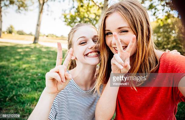 Two playful teenage girls making victory sign