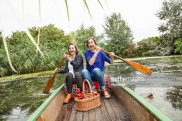 Two playful young woman in rowing boat