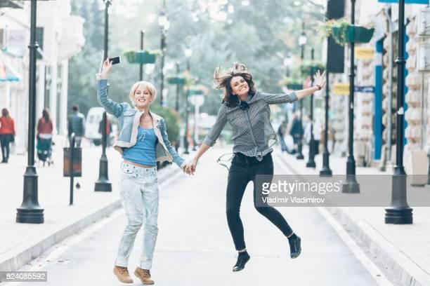 dos mujeres jóvenes juguetones saltando y divirtiéndose en la calle - 22 jump street fotografías e imágenes de stock