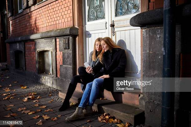 Two playful young women sitting on doorstep using phone