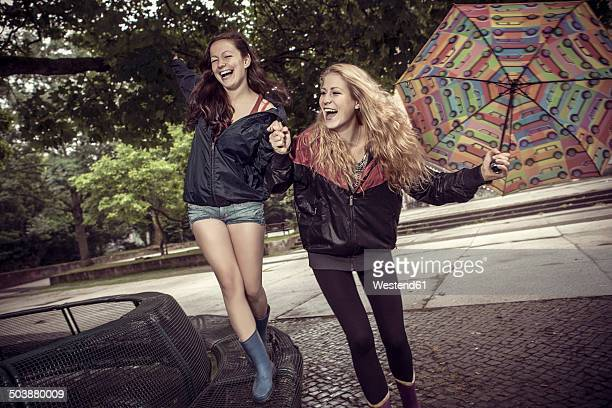 Two playful young women with umbrella in park