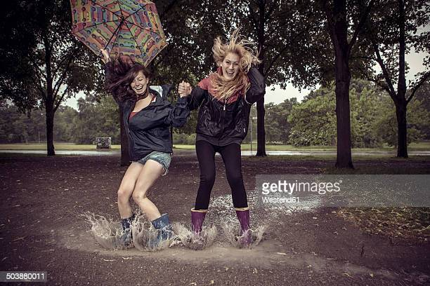 two playful young women with umbrella jumping in puddle - gummistiefel frau stock-fotos und bilder