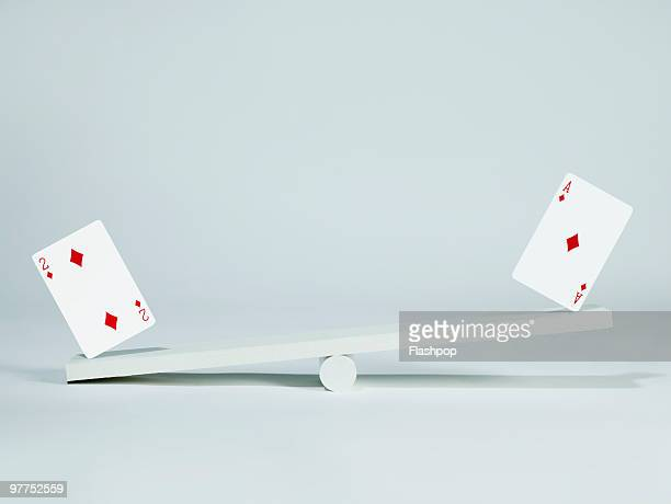 Two playing cards balancing on seesaw