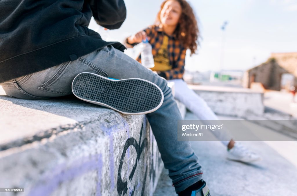 Two playing children sitting on a wall, partial view : Stock Photo