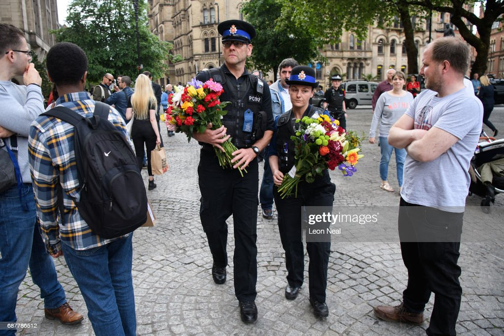 Two Police Community Support Officers (PCSO) deliver flowers to the location of many of the floral tributes on May 24, 2017 in Manchester, England. An explosion occurred at Manchester Arena on the evening of May 22 as concert goers were leaving the venue after Ariana Grande had performed. Greater Manchester Police are treating the explosion as a terrorist attack and have confirmed 22 fatalities and 59 injured.