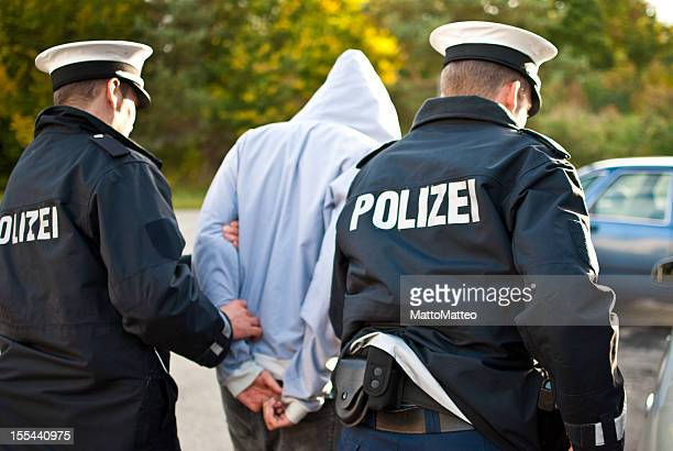 two police officers are frogmarching a suspect - germany stock pictures, royalty-free photos & images