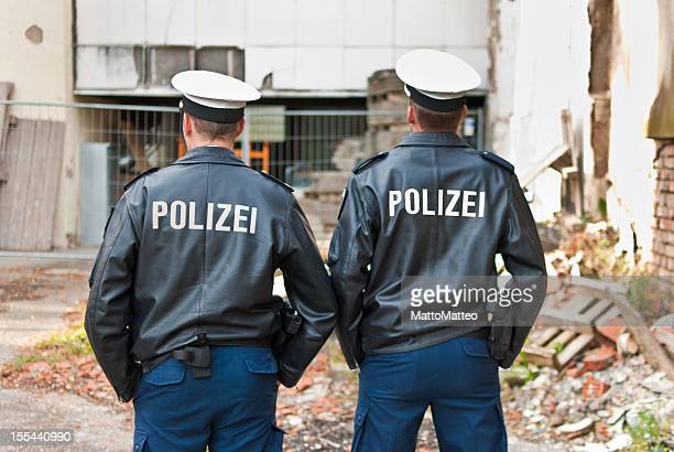two police officers are showing their back - duitsland stockfoto's en -beelden