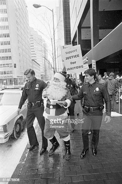 Two police officers arrest a man dressed as Santa Claus who distributed leaflets in a Denver bank involved in a labor dispute