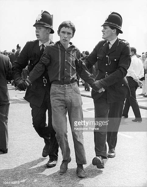 Two police officers arresting a Mod during the festivities of the Hastings Battle holiday in Kent on August 4 1964