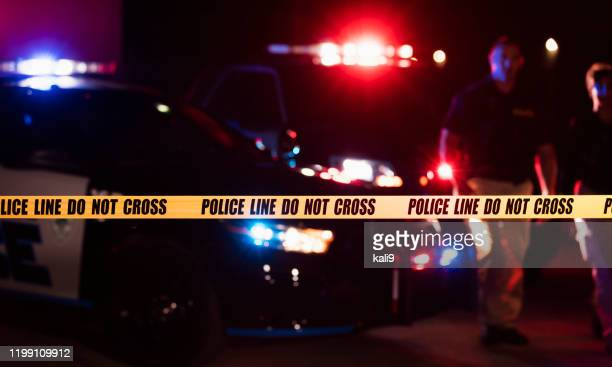 two police officers behind crime scene tape - police uniform stock pictures, royalty-free photos & images