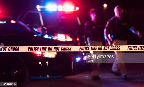 two police officers behind crime scene tape - police force stock pictures, royalty-free photos & images