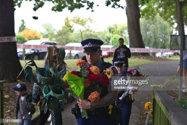 Two police officers carry flowers to the Masjid Al Noor Mosque in Christchurch New Zealand on March 17 2019 At least 50 people were reportedly killed...