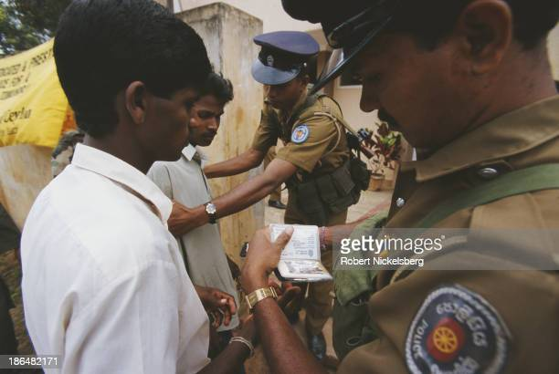 Two police officers check the identification of two men in Jaffna Sri Lanka circa 1998