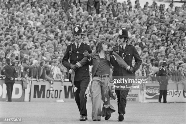 Two police officers escort a fan off the ground during a League Division Two match between Leyton Orient and Manchester United on Brisbane Road,...