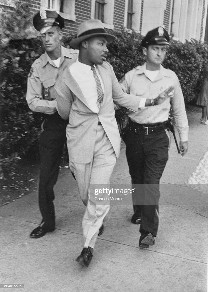 Two police officers escort American religious and Civil Rights leader Dr Martin Luther King Jr (1929 - 1968) away from the Montgomery Recorder's Court where he had been arrested for loitering, Montgomery, Alabama, September 3, 1958.