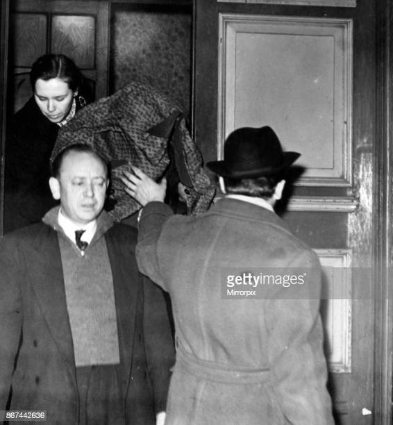 Two police officers escort Mrs Wilson her head covered by a raincoat from the hotel to a waiting car 12th December 1957