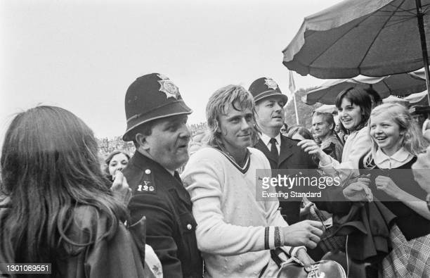 Two police officers escort Swedish tennis player Björn Borg past his fans during the Wimbledon Championships in London, UK, 29th June 1973.