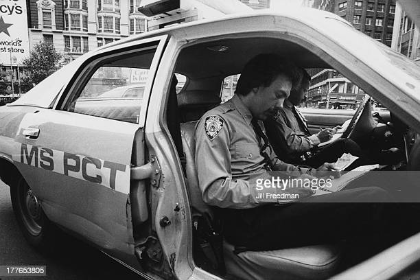 Two police officers fill out parking ticket paperwork in their patrol car parked in front of Macy's department store Midtown Manhattan New York City...
