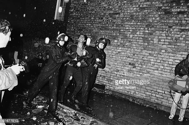 Two police officers in riot gear arrest a suspect during the riot on the Broadwater Farm housing estate Tottenham London 6th October 1985 The racial...