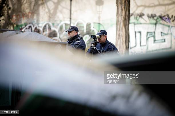 Two police officers measure the speed of road users with a speedometer on February 27 2018 in Berlin Germany