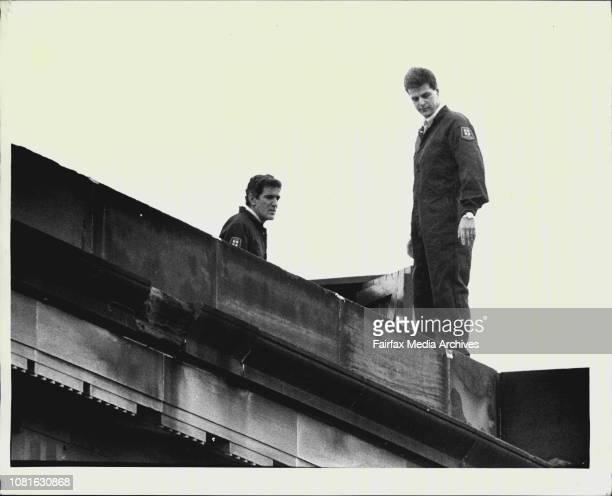 Two police officers on top of a court building combing the roof with metal detectors June 16 1987