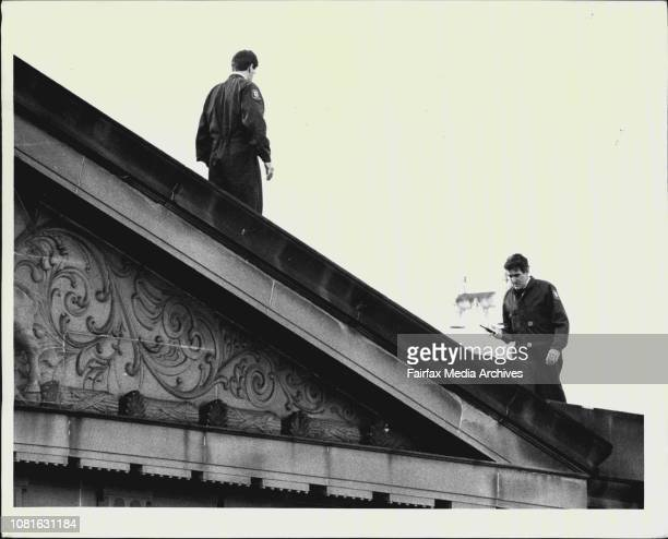 Two police officers on top of a court building combing the roof with metal detectors June 18 1987