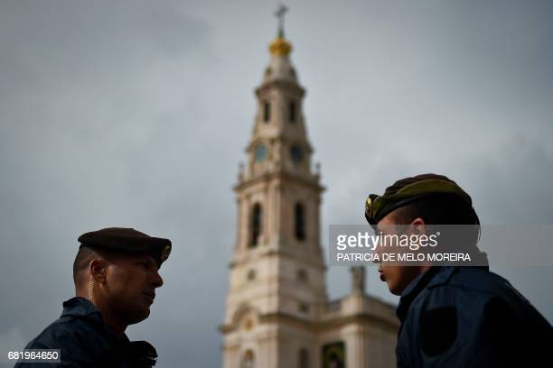 "Two police officers speak with the ""Nossa Senhora do Rosario de Fatima"" basilica on the background in Fatima, central Portugal, on May 11, 2017. Two..."