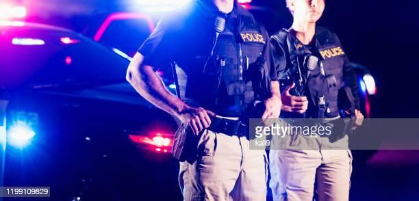 dois oficiais de polícia que estão na frente dos carros de patrulha - força policial - fotografias e filmes do acervo