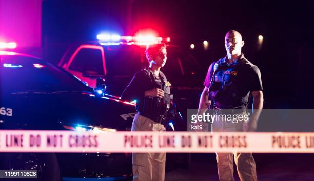 two police officers standing in front of patrol cars - crime scene stock pictures, royalty-free photos & images