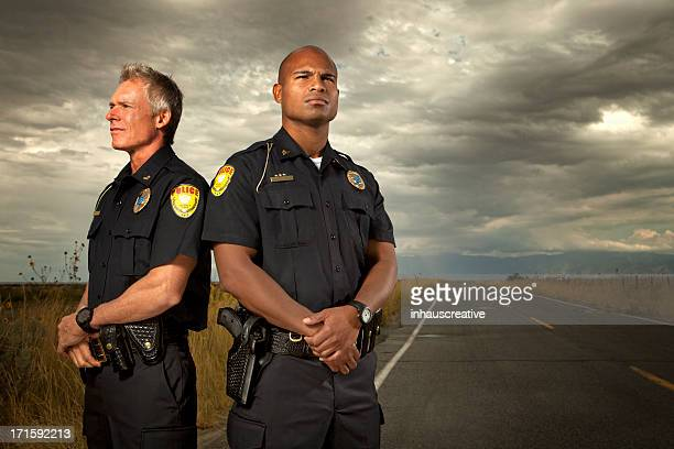 Two police officers standing on quiet road