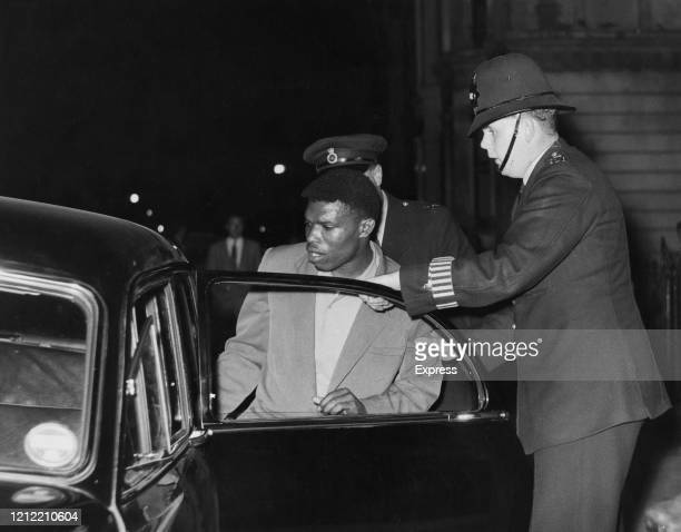 Two police officers take off a man in a police car during the Notting Hill race riots London UK 2nd September 1958