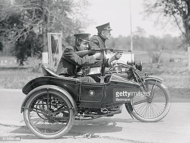 Two police officers take off in their motorcycle and sidecar The officer in the sidecar is aiming a Thompson submachine gun a Tommy gun and wearing a...