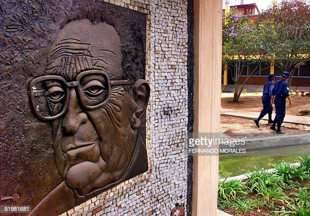 Two police officers walk 20 March 2001 by a bronze sculpture of Guatemalan bishop Juan Gerardi outside the parochial house where he was murdered 26...