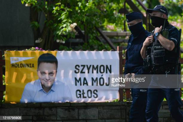 Two Police officers walk by an election poster of Szymon Holownia an independent candidate for the Presidential Election 2020 seen in Alwernia On...