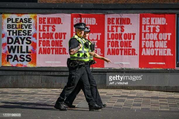 Two police officers walk past posters on Sauchiehall Street during the coronavirus lockdown on May 6, 2020 in Glasgow, Scotland. The country...