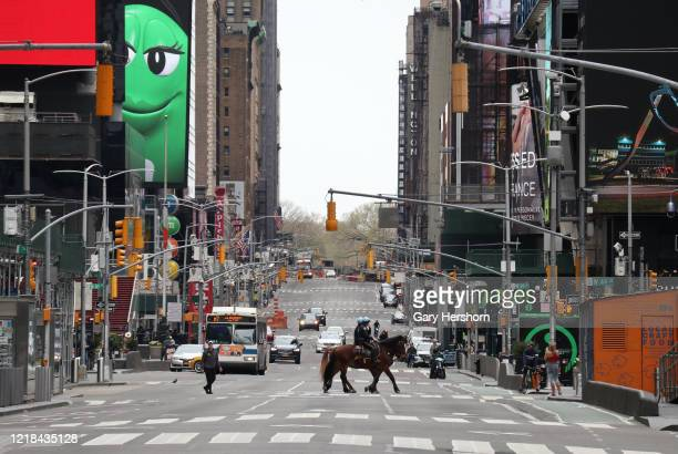 Two police officers walk their horses through a virtually empty Times Square on Easter Sunday on April 12 2020 in New York City