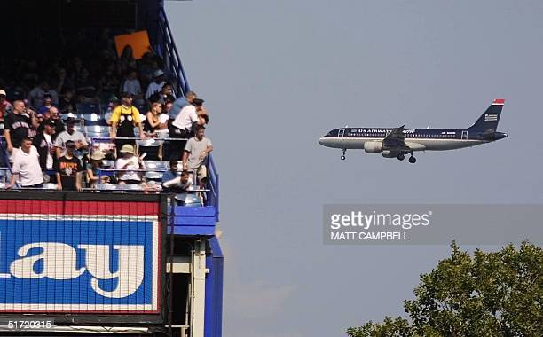 Two police officers watch from the edge of the stands as a US Airways flight passes by enroute to LaGuardia Airport during the baseball game between...